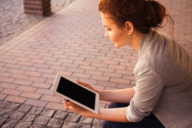 A woman looking at a tablet and thinking about how to protect your website from hackers.